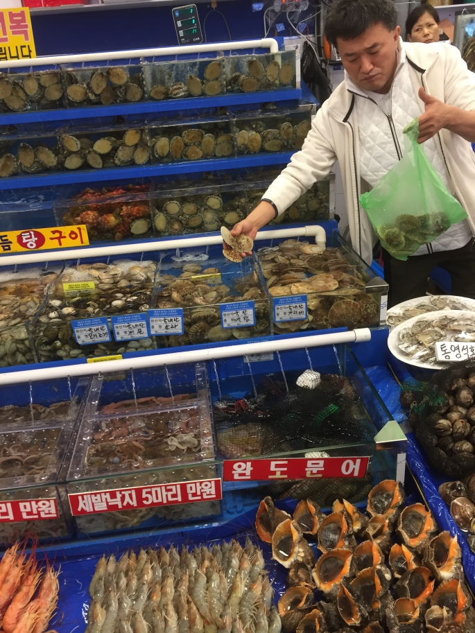 A man doling out scallops and octopuses at the fish market in Noryangjin